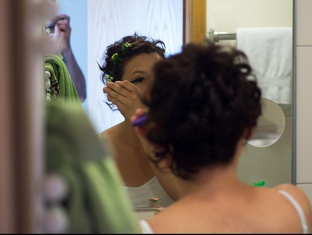 洗面所でメイクをするママ