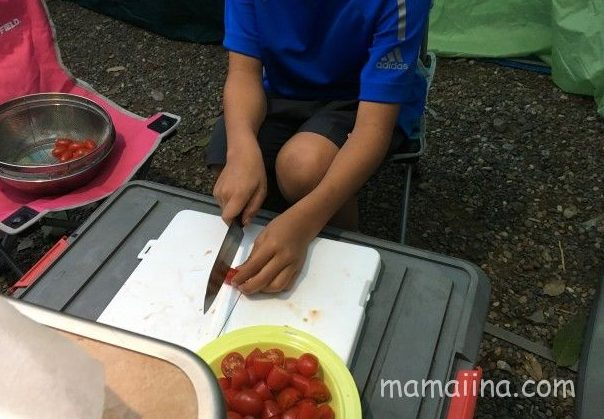 ピザに載せるミニトマトを子供がカット